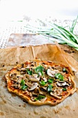 A mushroom pizza on a piece of baking paper