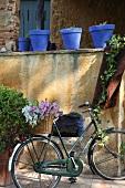 Fahrrad mit Blumen im Korb an abgeblätterter Mauer