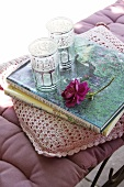 Seat cushions, scatter cushion with crocheted cover, books, glasses and a rose