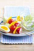 Vegetable kebabs with egg and a cucumber salad