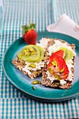 Crispbreads topped with cottage cheese, strawberries, kiwis and pistachios