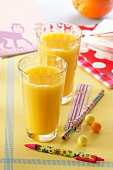 Two glasses of orange juice and school things