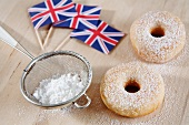 Doughnuts dusted with icing sugar with Union Jacks in the background
