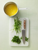Herbs being chopped and butter being boiled