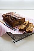 Partially Sliced Loaf of Banana Bread on a Cooling Rack with a Knife