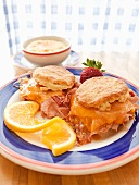 Two Buttermilk Biscuit Breakfast Sandwiches with Ham and Cheddar Cheese; Cheese Grits