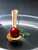 A cherry on a wooden spoon