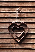 A decorative heart hanging on a wooden wall