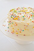 An orange and pineapple cake topped with cream cheese and decorated with sugar confetti