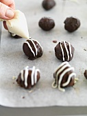 Chocolate pralines being decorated with white chocolate stripes