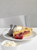 A slice of raspberry and apple shortcake with cream