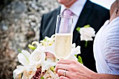 A bride and groom with a glass of champagne and a bouquet