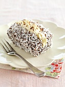 A lamington with buttercream (cake with chocolate glaze and dessicated coconut)