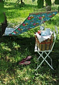 Picnic basket on chair and hammock hung between two trees