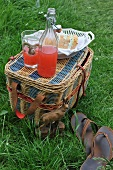 A picnic basket with sparkling juice and sandwiches