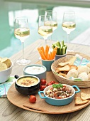 Dips, bread, vegetable crudités and wine by a swimming pool