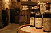 Dusty bottles on barrel in wine cellar with stone walls