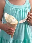 A girl holding a cone of banana ice cream