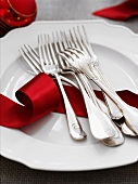 Forks and a red ribbon on a white plate