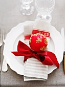 A napkin with a red ribbon and a Christmas bauble on a white plate