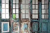 Abblätternde Farbe an Holzwand mit Sprossenfenstern und Türen