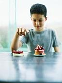Junge sitzt mit Törtchen am Tisch