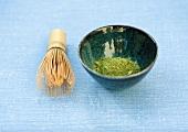 Bowl of macha tea powder and tea whisk
