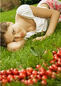 Woman lying in grass, cherries in foreground