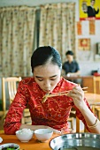 Young woman wearing traditional Chinese clothing, eating with chopsticks
