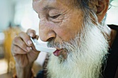 Elderly man with long beard eating with Chinese soup spoon