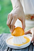 Woman pressing orange with citrus press, close-up, cropped view of hands