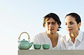 Couple outdoors, looking at tea set, smiling