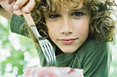 Boy picking up piece of meat with fork, looking at camera