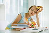 Girl eating sweets and doing homework