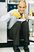 Man sitting in front of open refrigerator, putting mustard on hamburger