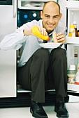 Man sitting in front of open refrigerator, putting mustard on hamburger