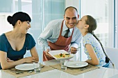 Man serving wife and daughter spaghetti, girl kissing father on cheek