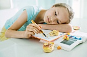 Girl sitting at table doing homework, resting head on arm, doodling, food scattered on books