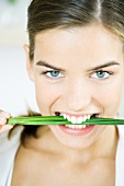 Woman holding chives between teeth, smiling at the camera, portrait