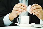 Professional man preparing cup of coffee, cropped view of hands