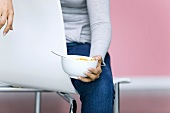 Young woman holding bowl of cornflakes, cropped