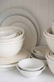 Assorted white dishes stacked in a cupboard
