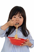 Girl eating spaghetti from bowl