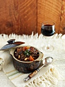 Beef stew with carrots and a glass of red wine