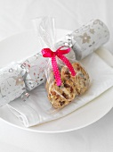 A Christmas cracker and a cellophane bag of biscuits on a plate