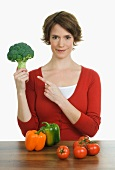 Woman with broccoli, pepper and tomatoes