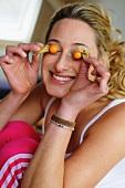 Junge Frau bedeckt ihre Augen mit Obst