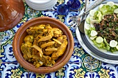 Chicken tagine and aubergine puree on table tiled with Oriental pattern