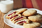 Raspberry Jam Stuffed Pillow Cookies on a Platter; Glass of Milk