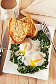 Two Fried Eggs Served Over Sauteed Spinach with Toast and Coffee